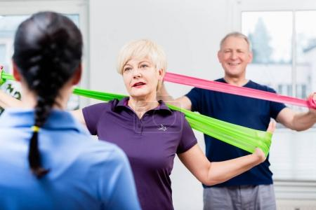 Elderly couple in senior gymnastic class doing workout with rubb