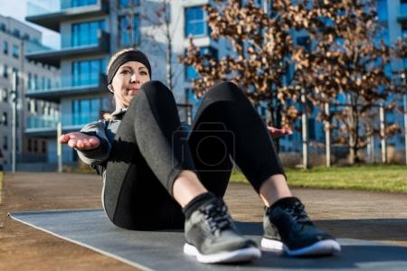 Young woman doing crunches with raised up palms for the abdomina