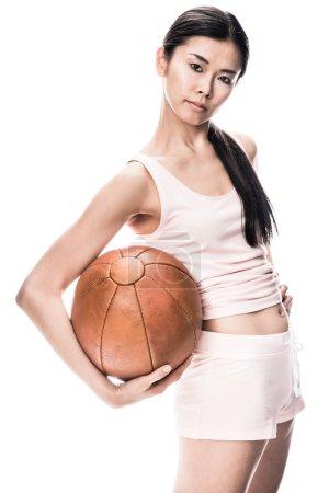 Photo pour Young fit femme asiatique en regardant la caméra tout en maintenant le médecine-ball brun - image libre de droit