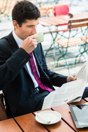 Homme d'affaires, lire un journal et de boire du café dans le morni