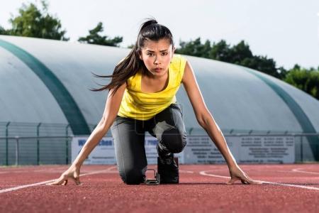 Photo for Female Runner before start signal on starting block of sprint track in sport stadium - Royalty Free Image