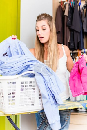 Woman in front of wardrobe in bedroom folding laundry