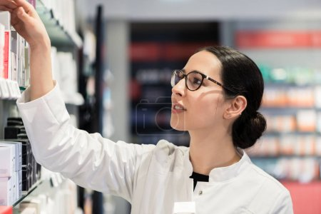 pharmacist standing in front of various products thinking to mak