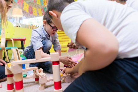 Cute boy building with attention and patience a wooden structure