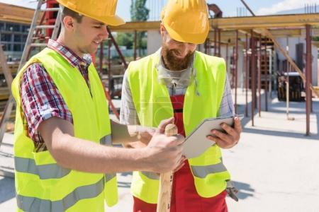 Two young construction workers smiling while using a tablet duri