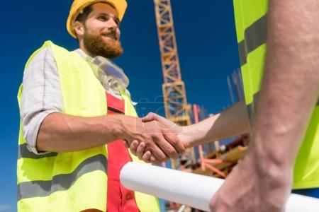 Cheerful worker shaking the hand of an architect at the beginnin