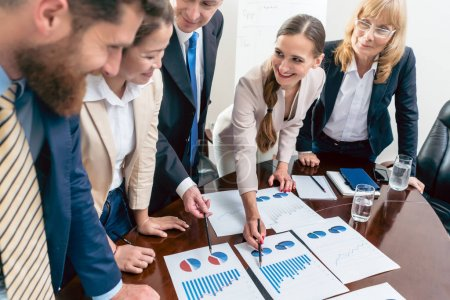 Multi-ethnic team of five dedicated specialists smiling while an