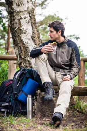 Hiker taking food break in shade of tree