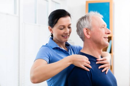Photo for Masseuse applying neck massage on older man - Royalty Free Image