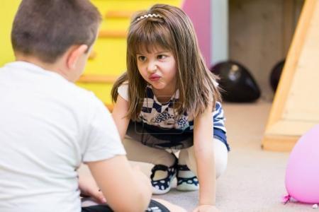 Photo pour Petite fille mignonne faisant un drôle de visage tout en regardant un garçon avec hostilité pendant le temps de jeu à la maternelle - image libre de droit