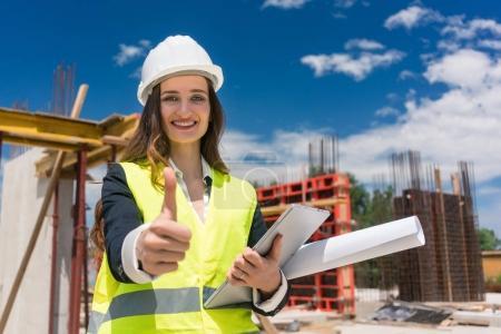 Photo pour Portrait d'une femme heureuse contremaître de construction ou architecte montrant pouce levé tout en tenant une tablette et le plan d'un bâtiment en construction - image libre de droit