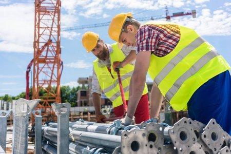 Photo pour Deux employés ouvriers efficaces préparent les fournitures avant de construire un échafaudage métallique tout en travaillant ensemble sur le chantier de construction - image libre de droit