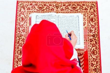 Muslim woman studying Koran or Quran