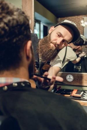 Photo pour Vue de côté du gros plan de la tête d'un jeune homme et entre les mains d'un coiffeur qualifié tailler sa barbe, avec peigne et ciseaux dans un salon de coiffure cool - image libre de droit