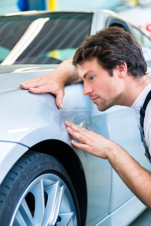 Male mechanic examine car
