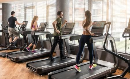 Group of four people running on treadmills in fitness gym