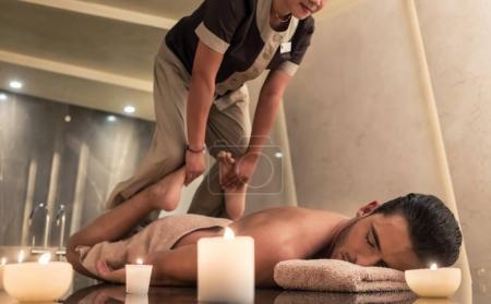 Photo pour Thai massage praticien massage jeune homme par le biais de techniques d'étirement traditionnels dans un centre de spa et de bien-être de luxe - image libre de droit