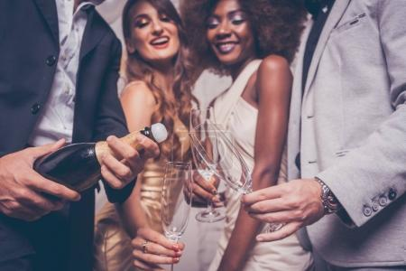 Man opening champagne bottle on celebration in club