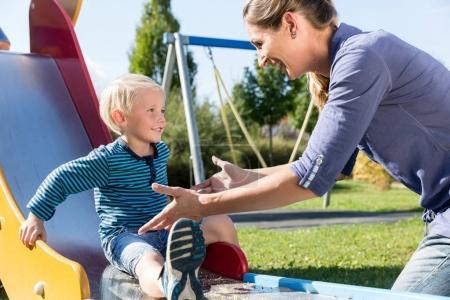 Photo pour Femme et petit garçon glissant vers le bas glissent à l'aire de jeux à l'extérieur - image libre de droit