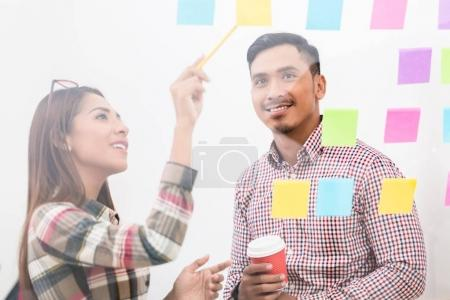 woman helping colleague with projects in office