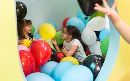 Two cute girls talking while playing with multicolored balloons