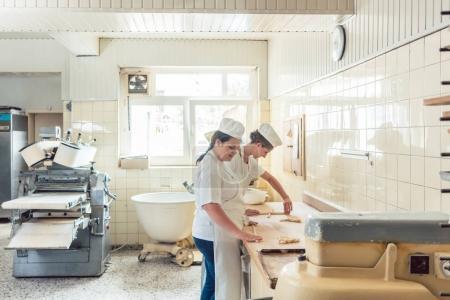 Photo pour Vue d'ensemble de la production de pain en boulangerie avec deux femmes travaillant - image libre de droit