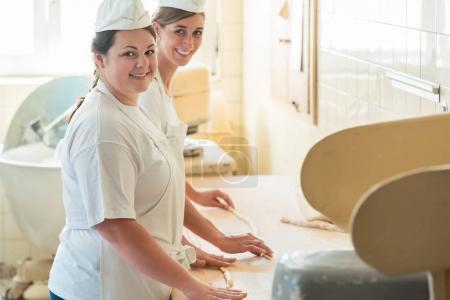 Photo pour Baker femmes travaillant dans la boulangerie de boulangerie regardant dans la caméra - image libre de droit