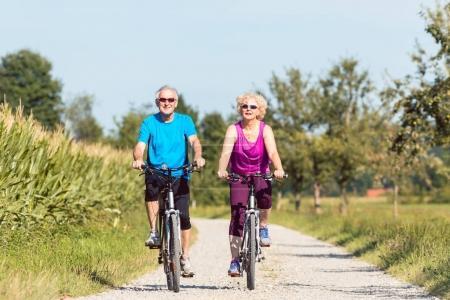 Active senior couple enjoying retirement while riding bicycles i