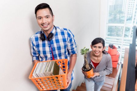 Young asian couple carrying belongings to new apartment