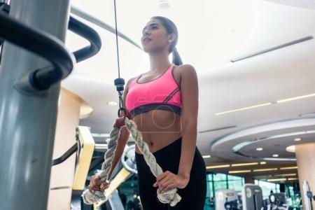 Low-angle view of a beautiful woman exercising cable rope tricep