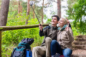 Man and woman hiking taking selfie