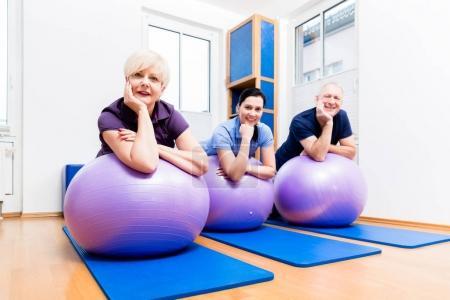 Physio showing senior couple exercises
