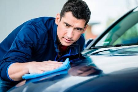 Young man polishing blue car