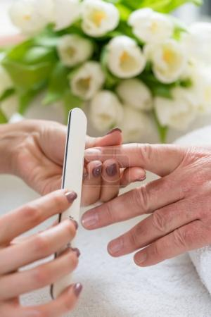 qualified manicurist filing nails