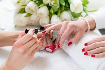 Hands of a skilled manicurist applying red nail polish on the na