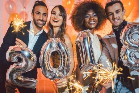 Couples in club celebrating new years eve dancing into midnight with sparkling wine