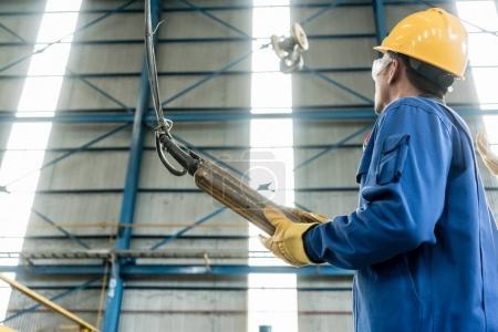 Photo pour Vue en angle bas d'un ouvrier asiatique qualifié contrôlant le crochet industriel pour le levage - image libre de droit