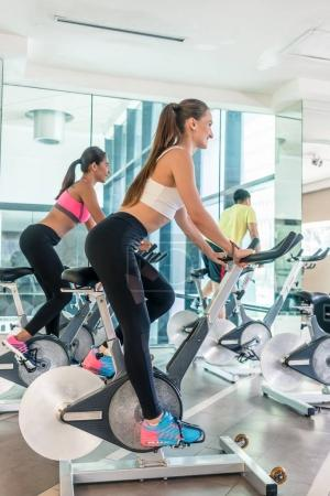 Side low-angle view of two cycling fit women