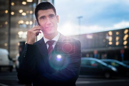 Business man using phone in evening outdoors