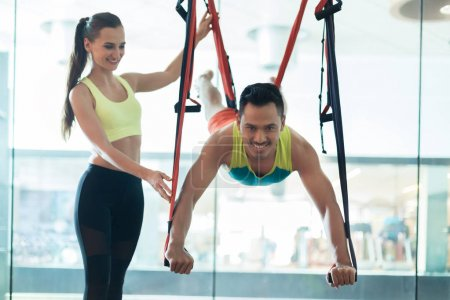 Cheerful young man hanging while practicing flying yoga with workout instructor