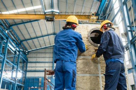 Foto de Dos trabajadores asiáticos aplicando material de aislamiento a una caldera de vapor industrial - Imagen libre de derechos