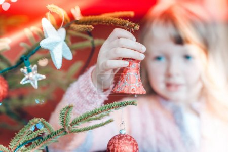 Young girl decorating the Christmas tree, holding some Christmas