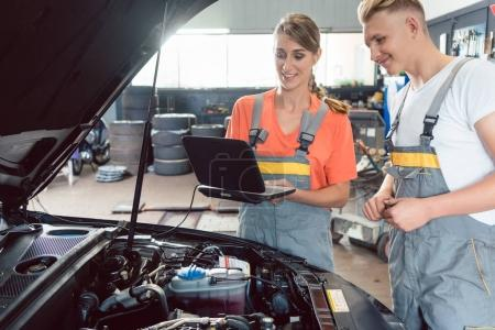Experienced female auto mechanic checking the engine error codes