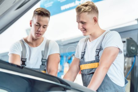 Experienced auto mechanic checking the parts of a car in a moder