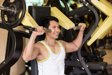 Strong young man exercising for arms muscles at a fitness club w