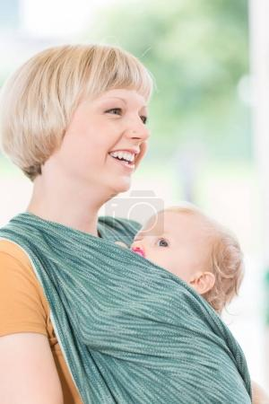 Young mum with child in baby sling for better mother-child bondi