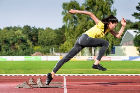 Photo for Female sprinter leaving starting blocks on running track in stadium - Royalty Free Image