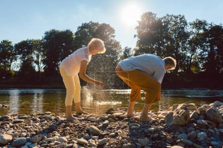 senior people throwing stones into river