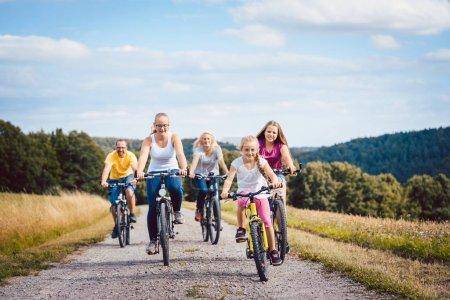 Family riding bicycles on afternoon in countryside