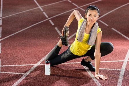 Photo for Woman sprinter doing warm up exercise before sprint in stadium - Royalty Free Image